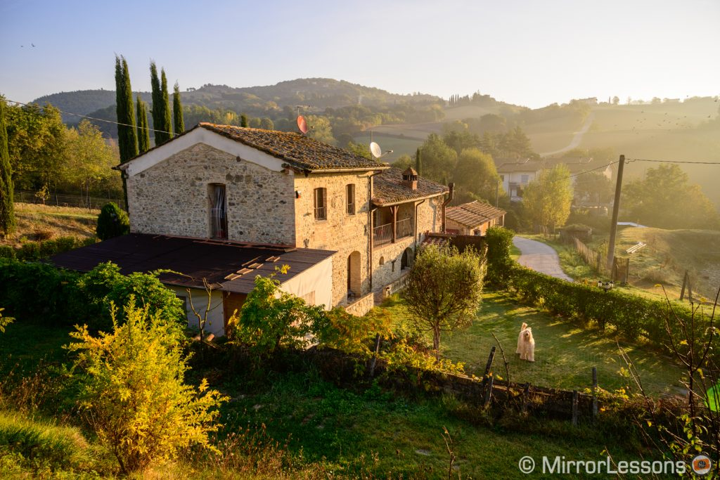 farm on a hill at sunrise in the Italian countryside