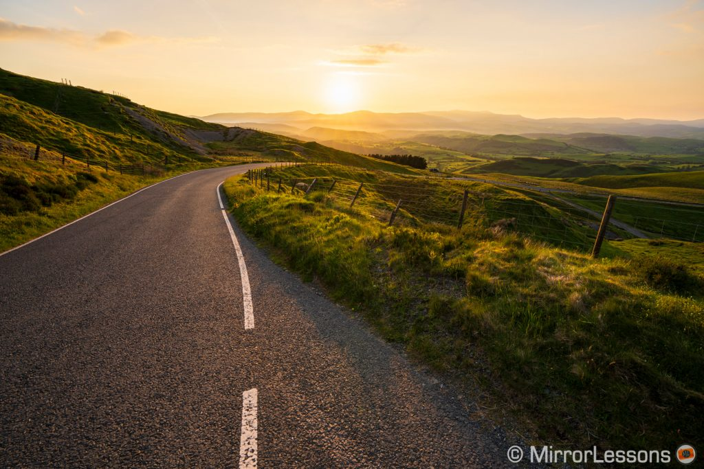 sunset landscape image with country road hills and mountains in the distance