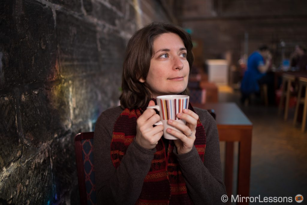 woman holding her cup of tea in a cafe bar, looking on the right