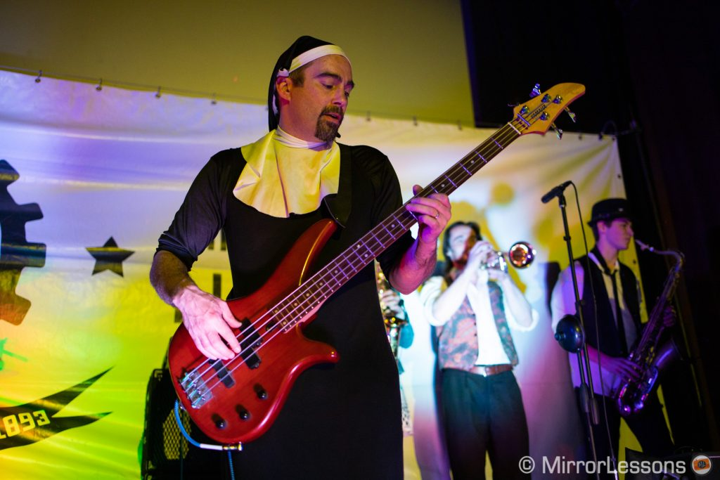 bass player dressed as a nun playing at a rock concert