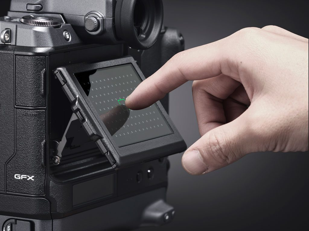 hand touching the rear LCD screen of the GFX100