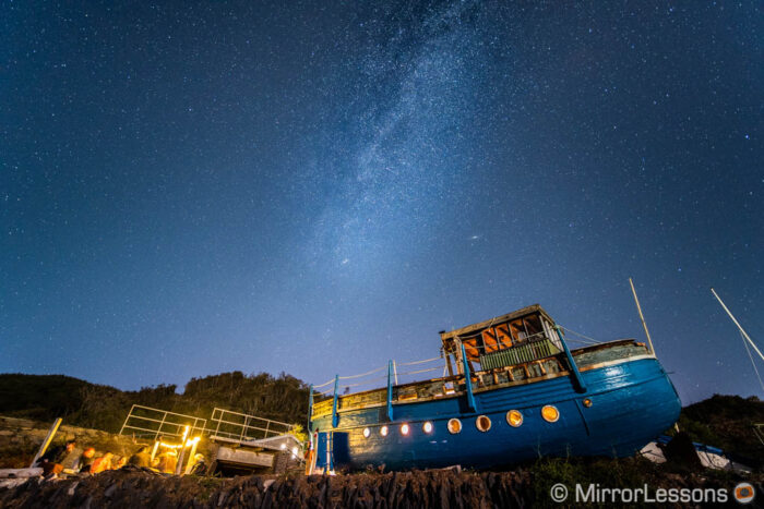 starry sky with milky way at the centre and an old blue wooden boat in the foreground.