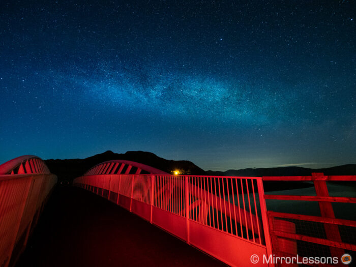 milky way in the blue starry sky in the background, and a modern bridge light-painted in red on the foreground