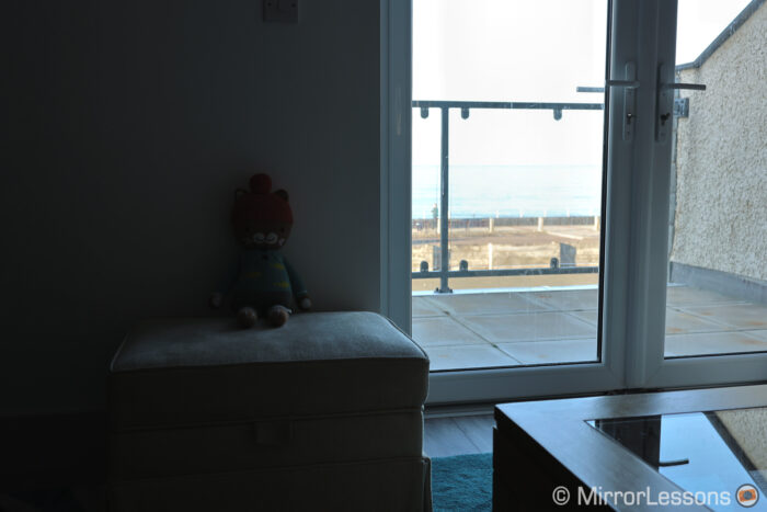 living room with window on the right showing outdoor balcony and sea in the background