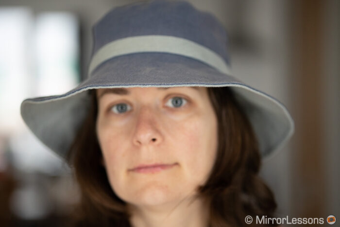 out of focus portrait of a woman wearing a summer hat