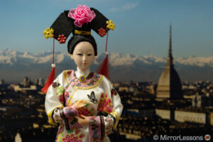 Japanese doll in front of the photo of a city panorama in the background. The image is darker than the next one.