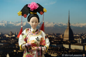 Japanese doll in front of the photo of a city panorama in the background. The image is brighter than the previous one.