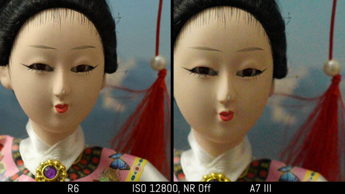 crop of the japanese doll out of camera JPEG image to show the difference in noise at 12800 ISO with noise reduction set to Off