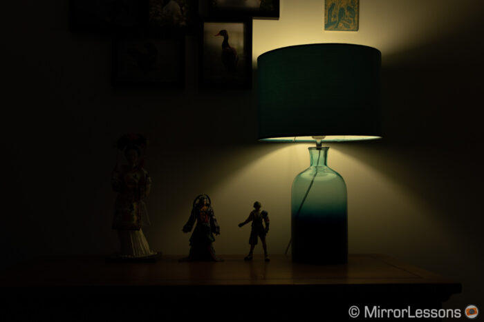 one japanese doll and two final fantasy action figures next to a lamp, on a chest of drawer. The image is visibly underexposed.