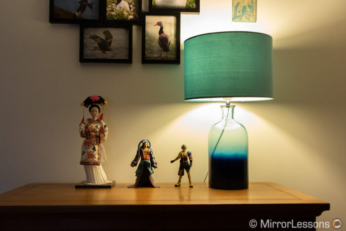 one japanese doll and two final fantasy action figures next to a lamp, on a chest of drawer. The image is correctly exposed.