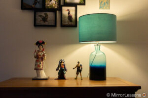 one japanese doll and two final fantasy action figures next to a lamp, on a chest of drawer. The image is correctly exposed and has more details in the bright areas.