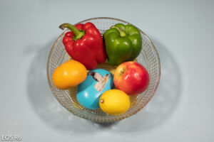 bowl of fruit and veg placed on a light blue mat, containing one orange, one red pepper, one green pepper, one apple, one lemon and a blue painted stone