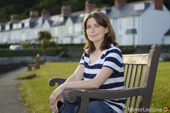 half-body portrait of a woman sitting on a bench, taken outdoor with houses in the background using the 50mm f2