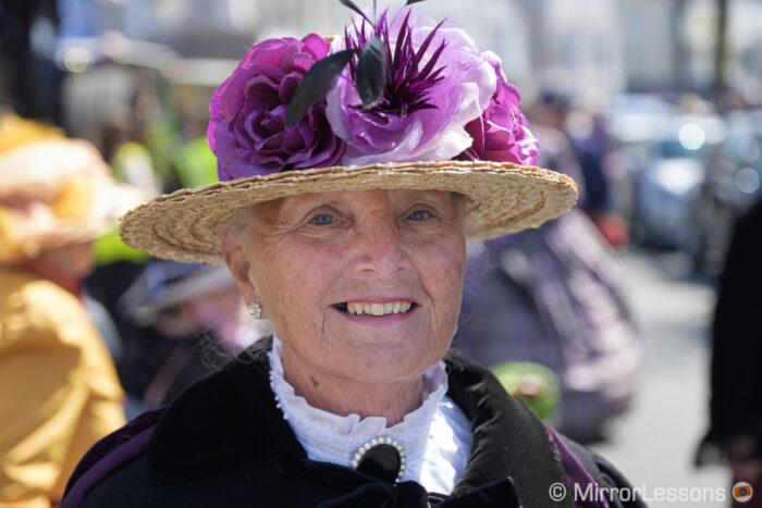 head-shot of a elderly woman wearing a hat with purple flowers, taken at the extravaganza festival with the 16-55mm