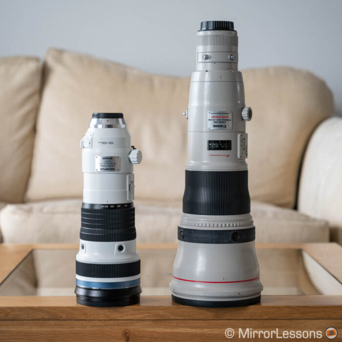Olympus 150-400mm Pro next to the Canon 800mm, standing on a wooden table