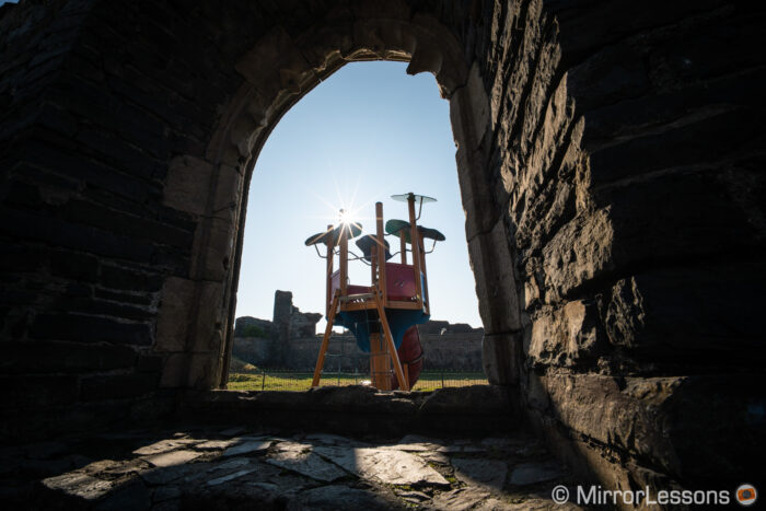 part of a kid's playground seen through the opening of an ancient castle wall