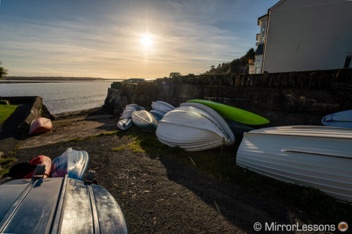 small boatyard with the sun in the background near sunset time