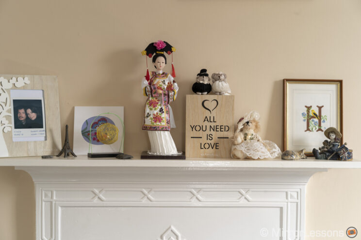 Japanese doll and other decoration elements standing on a shelf