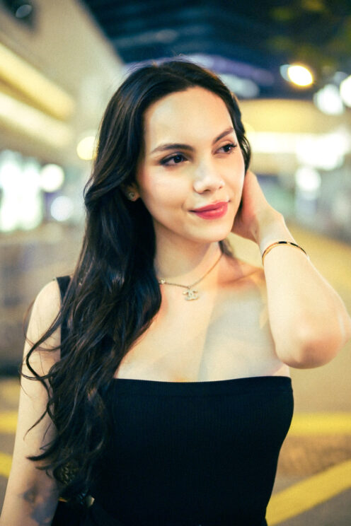 portrait of a woman with black hair and out of focus street at night in the background