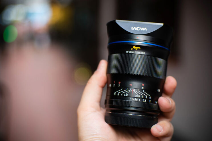 hand holding the Laowa 33mm lens with blurred background
