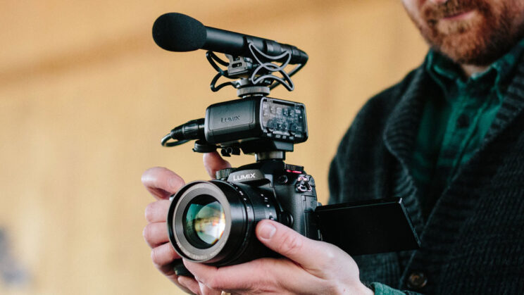 close-up on the GH5 II with XLR microphone mounded on the hot-shoe, held by the hands of a camera operator