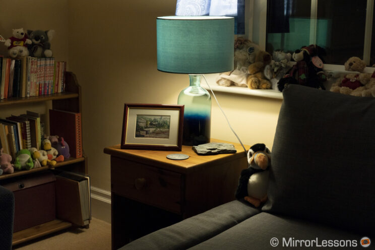 corner of a living room with lamp on side table