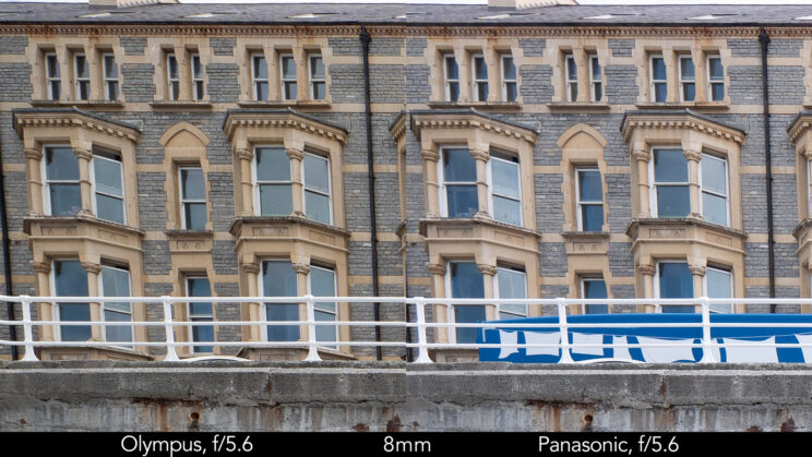 side by side enlargement of top left corner (details of the buildings) showcasing the quality at 8mm and f5.6 for the two lenses