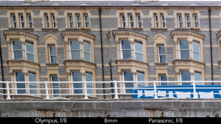 side by side enlargement of top left corner (details of the buildings) showcasing the quality at 8mm and f8 for the two lenses