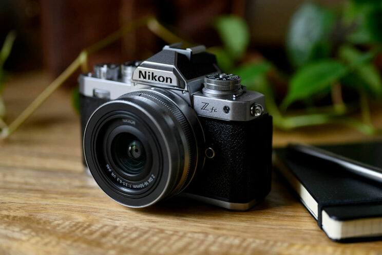 lifestyle image of the Nikon Z fc, sitting on a wooden surface next to a notepad