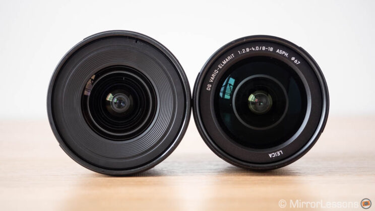 Olympus 8-25mm Pro and Panasonic 8-18mm side by side, showing the front of the lenses