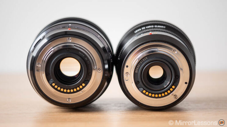 Olympus 8-25mm Pro and Panasonic 8-18mm side by side, showing the rear of the lenses