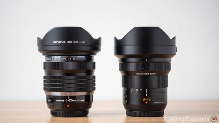 Olympus 8-25mm Pro and Panasonic 8-18mm side by side, with lens hood