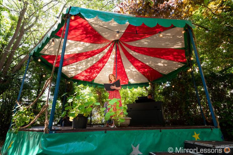 Opera singer performing in an outdoor garden, under a tent