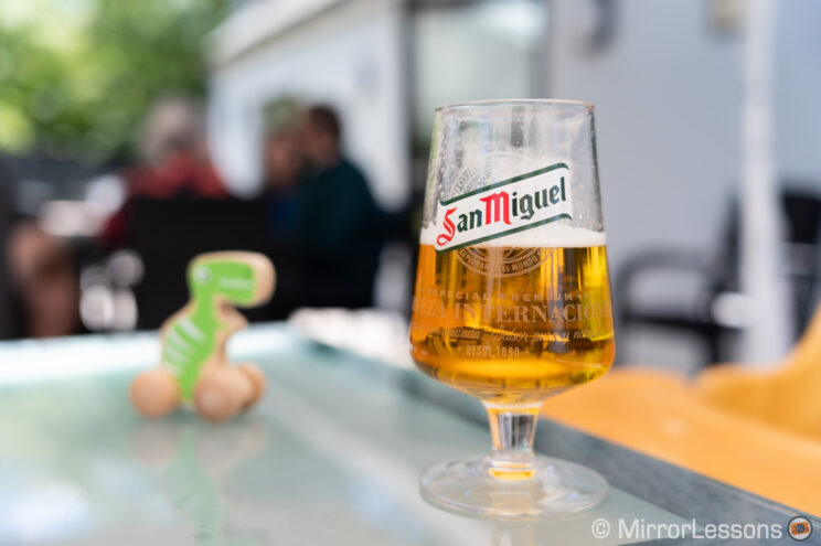 Full glass of San Miguel beer on a table in an outdoor restaurant, with background out of focus