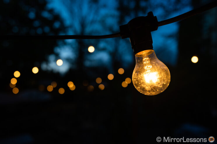 close-up on a light bulb hanging at night in an outdoor beer garden