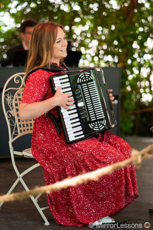 woman dressed in red playing the accordion outdoor