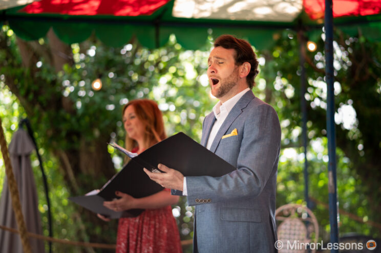 male opera singer performing outdoor in a beer garden, next to a female opera singer