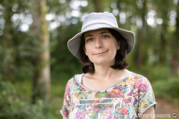 portrait of a lady wearing a hat in the woods
