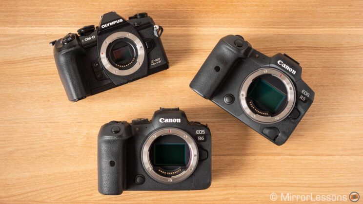 Olympus E-M1 III, Canon R5 and R6 on a wooden table, with sensor cap off