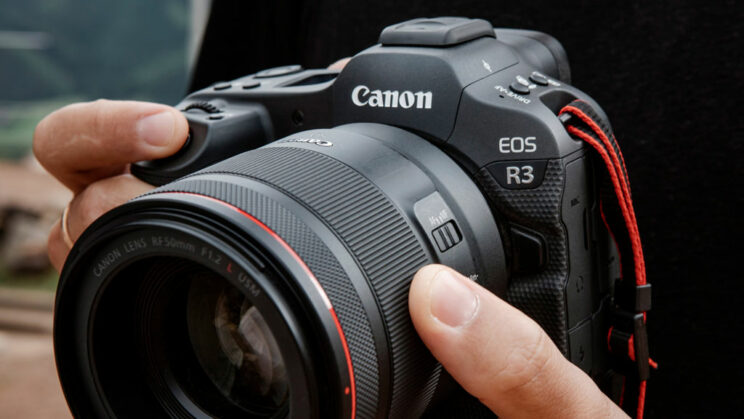 close-up on the Canon Eos R3 held by male hands