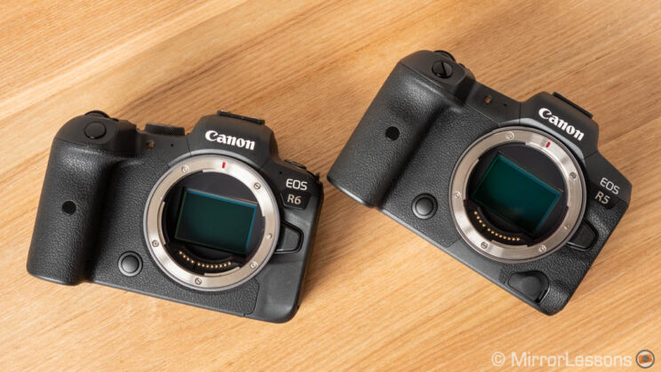 Canon R6 next to R5, with sensor cap off, on a wooden background