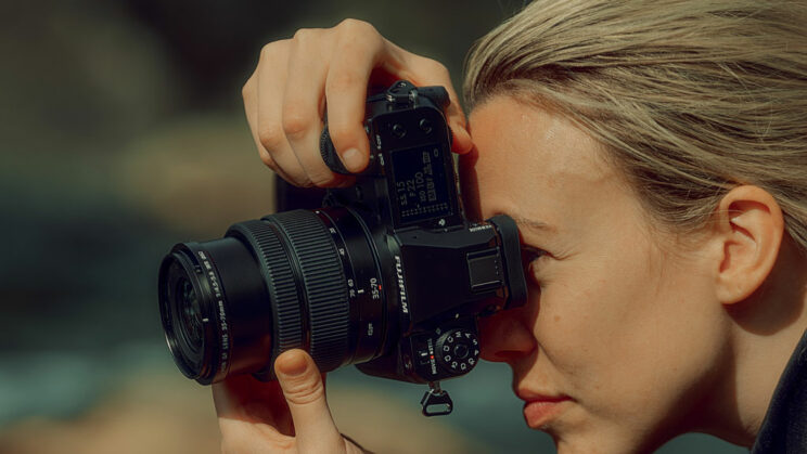 woman holding the GFX 50S II in vertical mode and looking through the viewfinder
