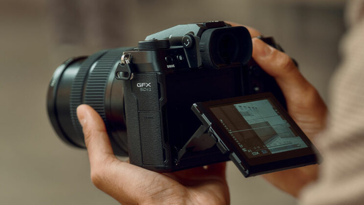 male hands holding the GFX 50S II with LCD screen titled