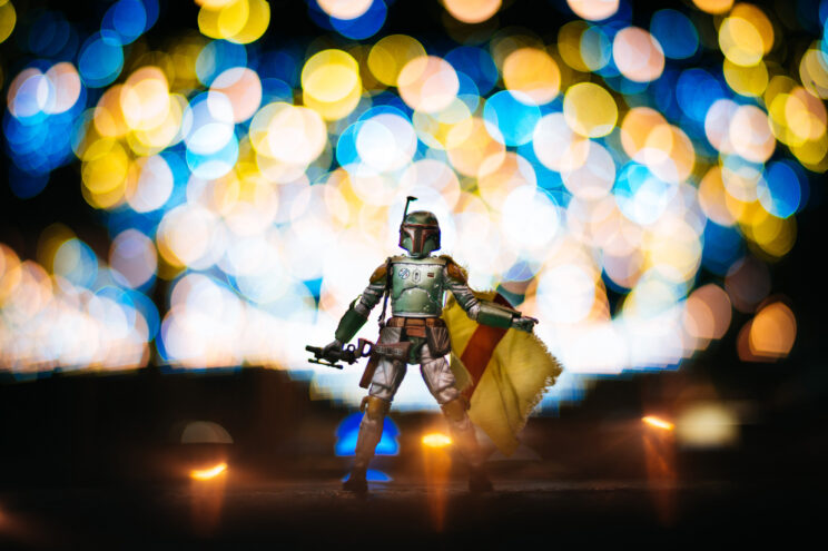 action figure of Star Wars' Boba Fett with coloured bokeh circles in the background