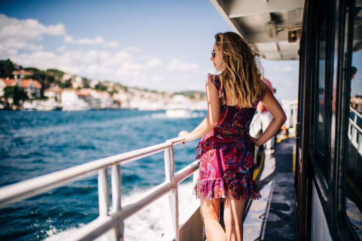 young blonde woman looking at the riviera cost from a boat