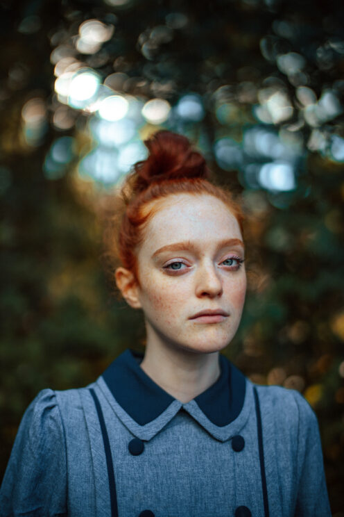 portrait of a young woman with red hair, and out of focus trees in the background