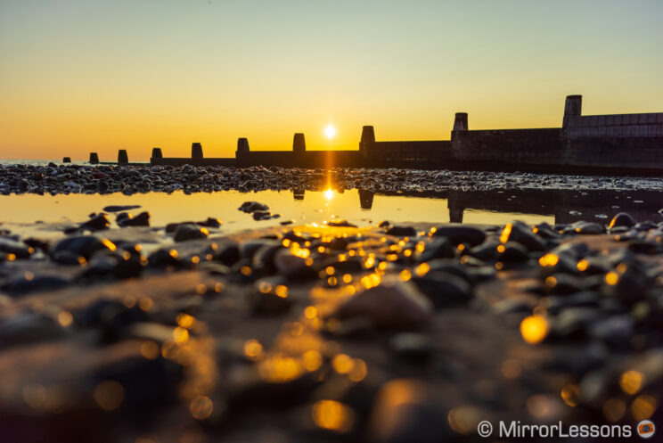 sunset on the beach with the camera low on the ground, highlighting wet rocks and sand on the foreground
