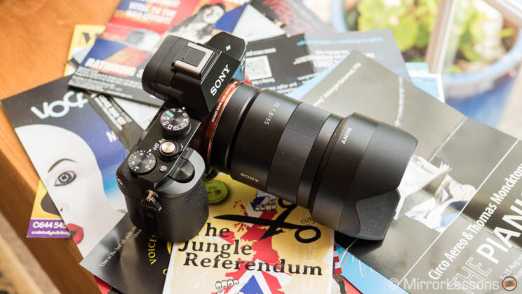 Sony A7S with 55mm F1.8 attached, resting on a small pile of magazines