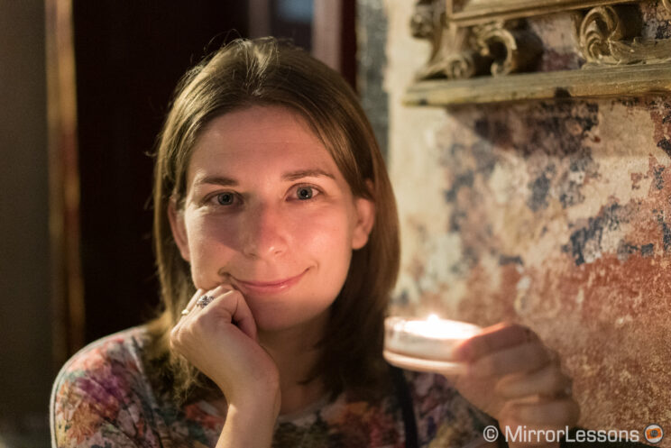 Headshot portrait of a young woman holding a candle in a low light location