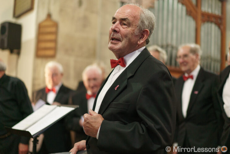 man singing with male choir in the background